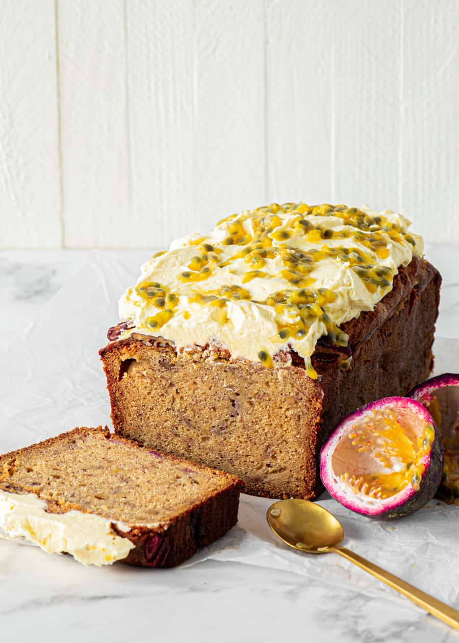 Banana bread loaf with cream cheese frosting and passionfruit drizzle.