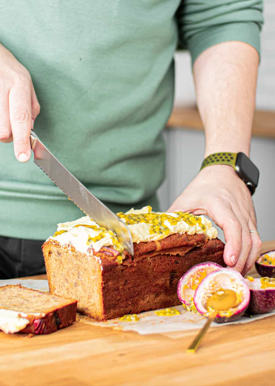 Slicing banana bread with cream cheese frosting and passionfruit pulp