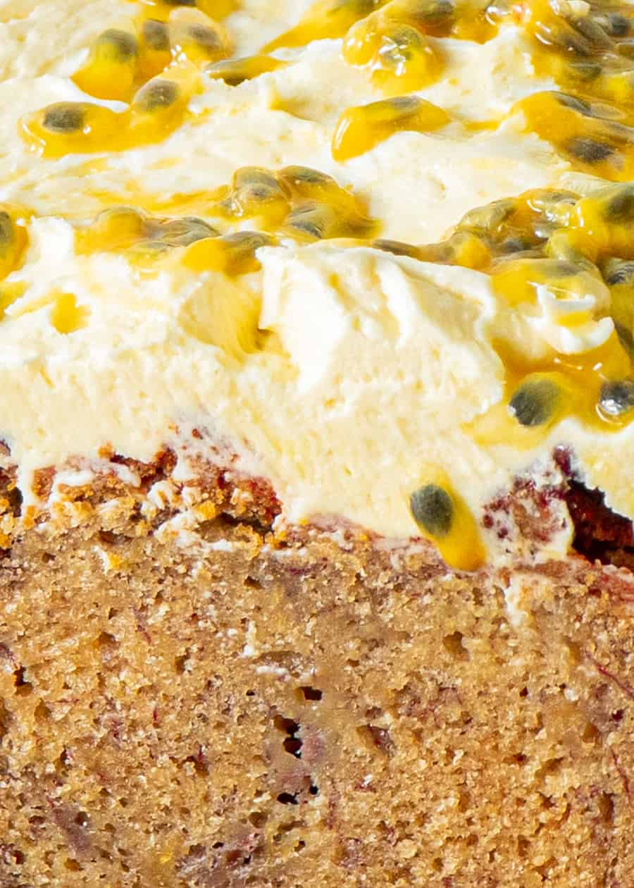 Close up of banana bread with cream cheese frosting and passionfruit pulp