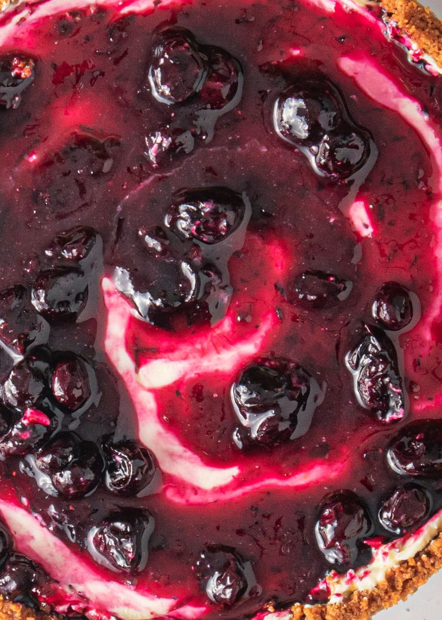 Close up of the top of a blueberry cheesecake with saucy and shiny stewed blueberries