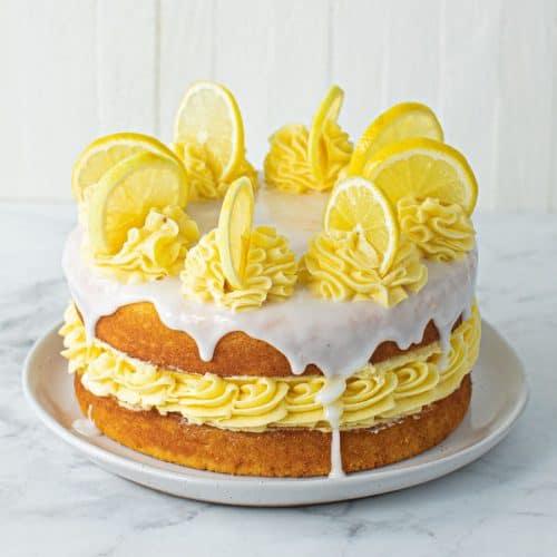 Full Lemon Sponge Cake on cake plate with lemon drizzle and slices