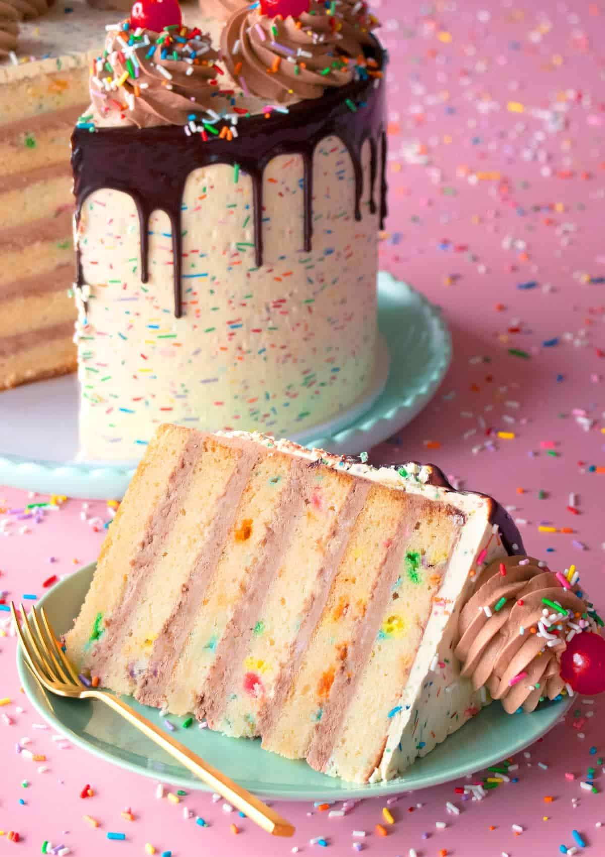 Slice of Classic Vanilla Funfetti Cake sitting on a plate.