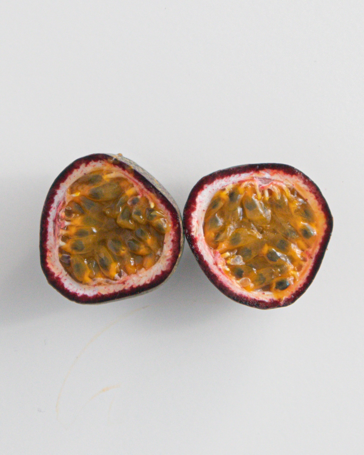 Passionfruit cut open on white background.