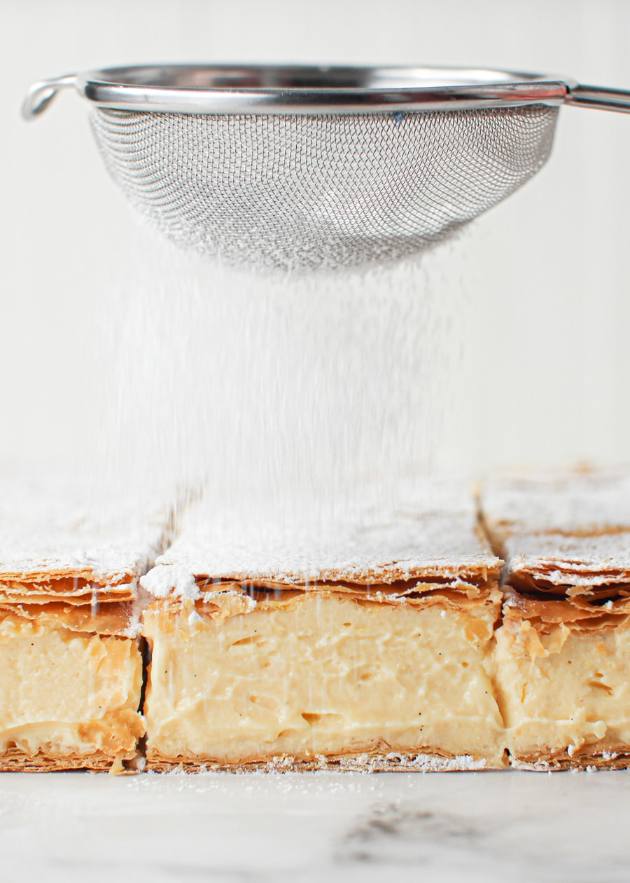 Classic Vanilla Slice with powdered sugar being dusted on.