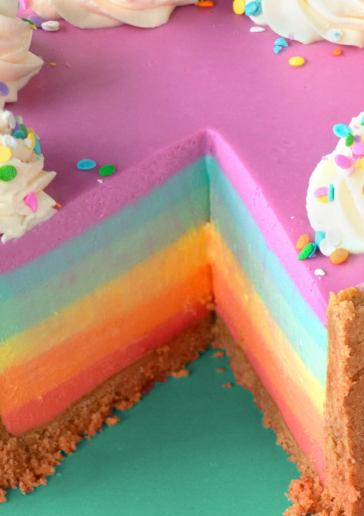 Close up of No-Bake Rainbow Cheesecake with slice taken out