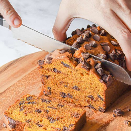 Hand cutting slices of Chocolate Chip Pumpkin Bread
